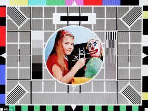 La mire anglaise avec la petite Carole devant un jeu de morpion, accompagnée d'une poupée clown
