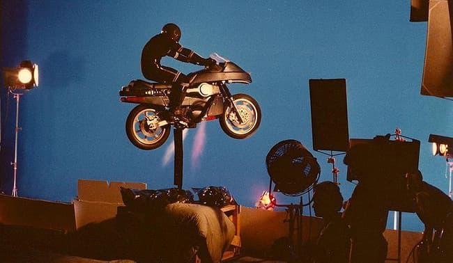 La moto et l'acteur de Tonnerre Mécanique, sur un support et devant un fond bleu pour une prise de vue de la série
