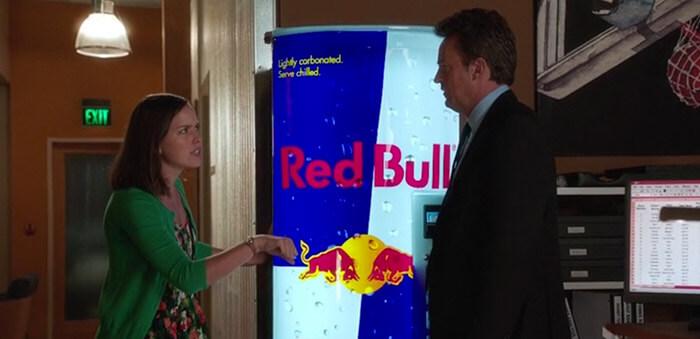 Deux personnages qui discutent devant un distributeur de boissons Red bull