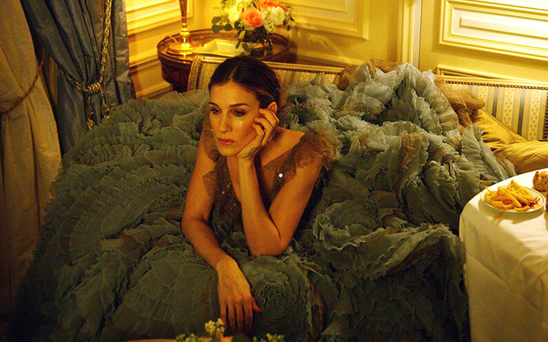 Carrie Bradshaw assise dans son encombrante robe Versace dans Sex and the city